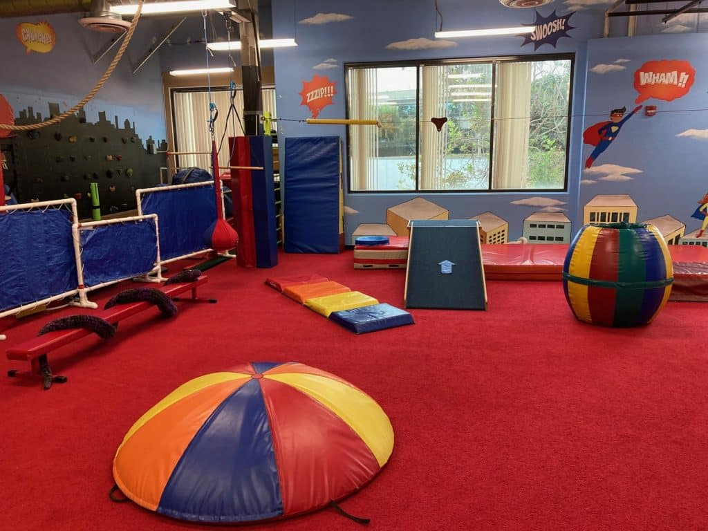 My Kids Place's colorful gym with balance beam, ramps, and swing | Physical Therapy in San Diego, CA