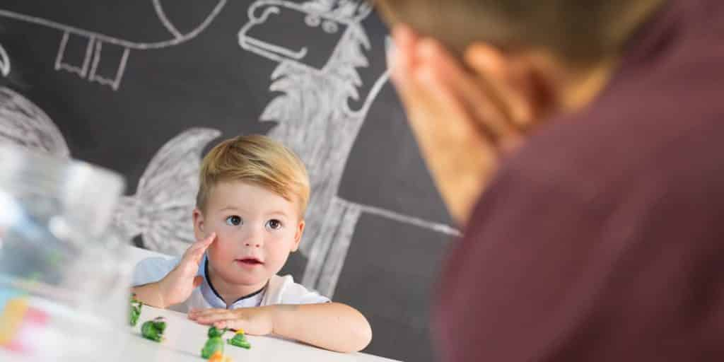 Child looking at teacher with small toys on table between them   social skills and overall child development