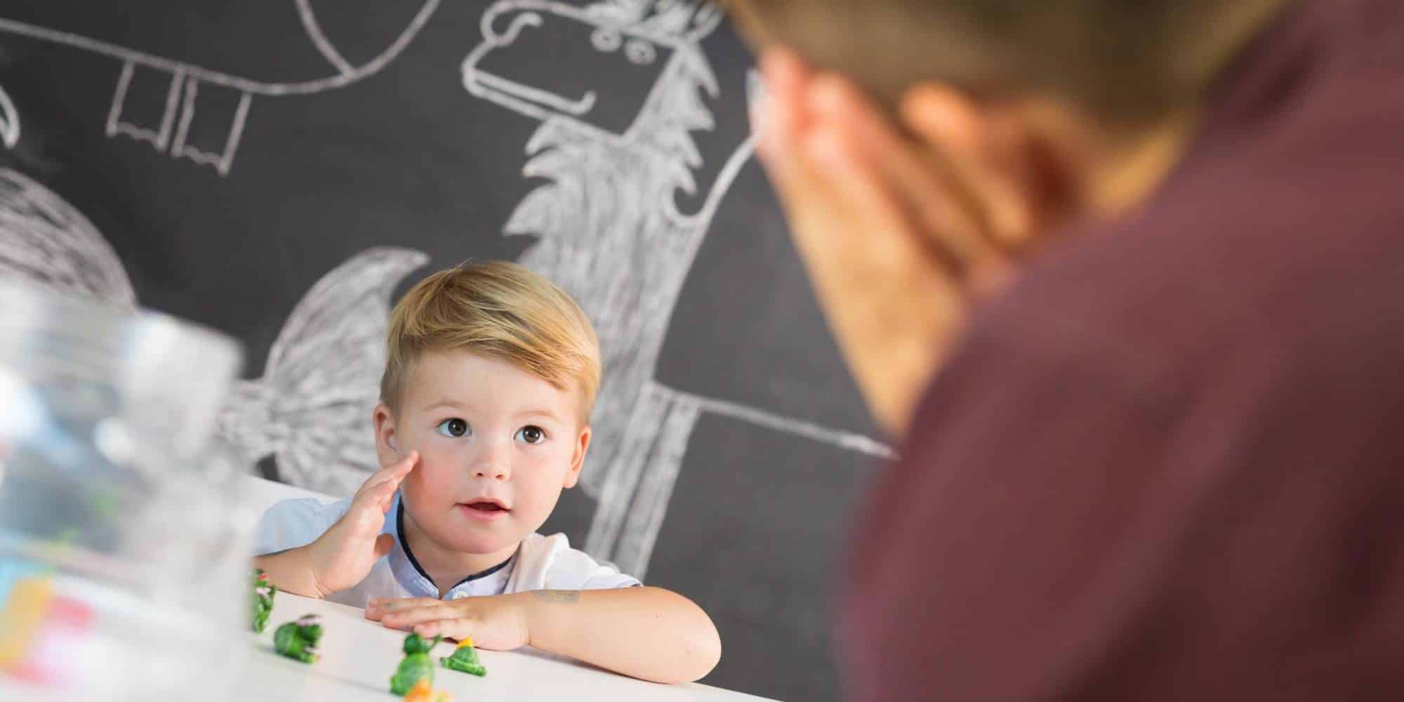 Child looking at teacher with small toys on table between them