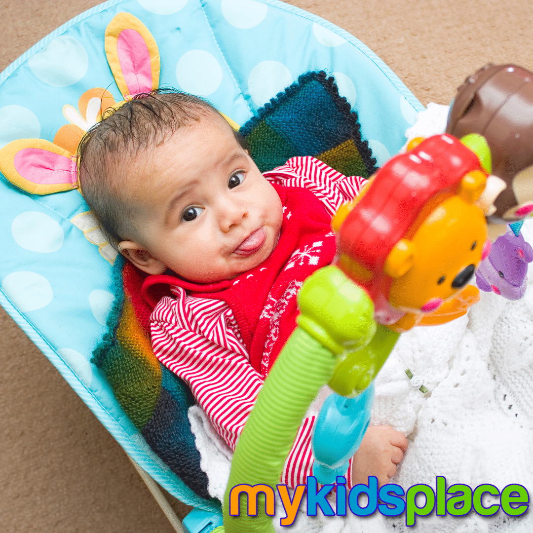 """A baby in a red outfit lies down in a colorful rocker """"container"""" while sticking tongue out at the camera."""
