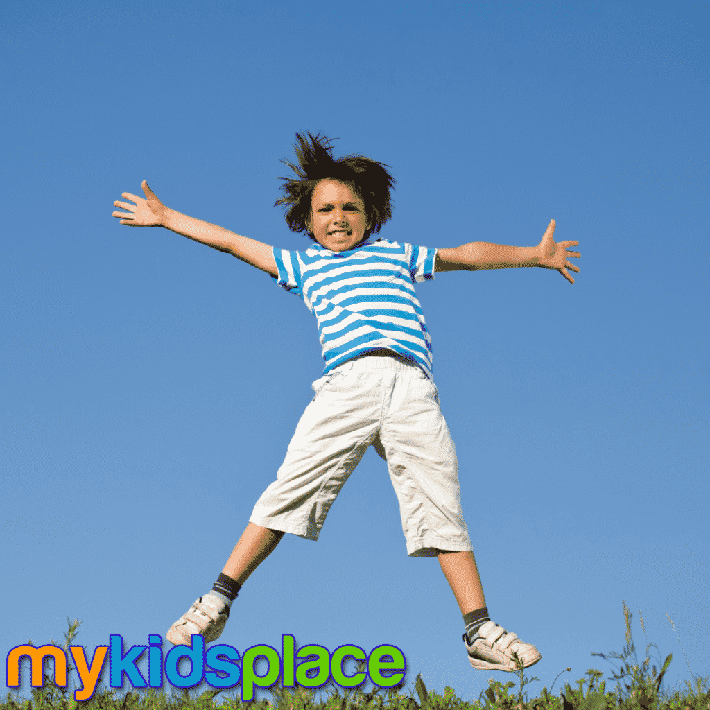 Child in striped shirt doing a jumping jack with arms and legs abducted.