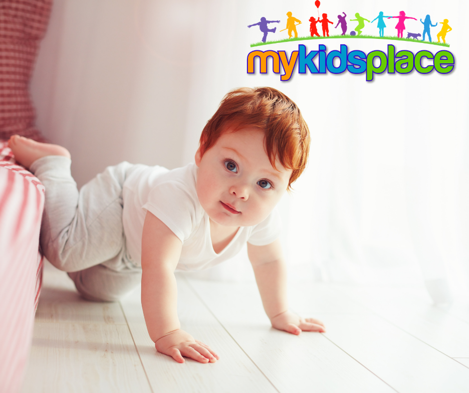 An infant with red hair wearing a white shirt and grey pants looks at the camera while creeps on hands and knees off of a low bed