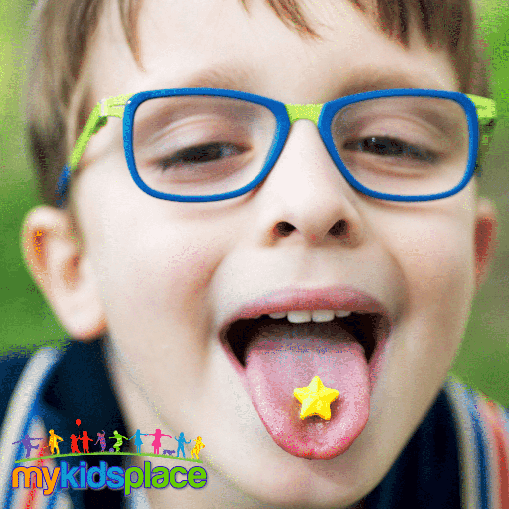 Child with glasses sticks their tongue out and is tasting a star shaped candy