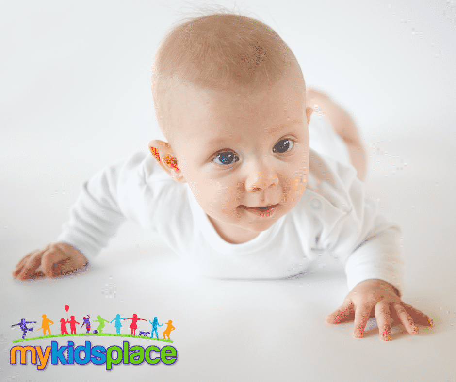 Baby in long-sleeve white onesie lies on belly on the floor with one arm in front and one arm to the side to help them crawl forward.