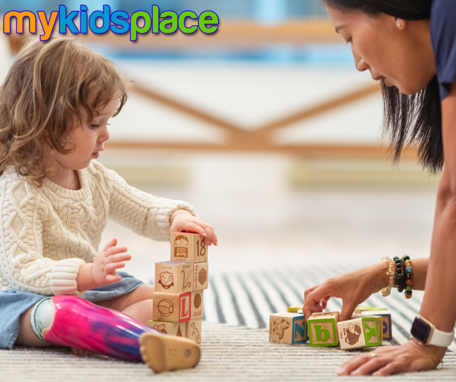 Child with prosthetic leg practices stacking blocks with an occupational therapist to improve their fine motor skills.