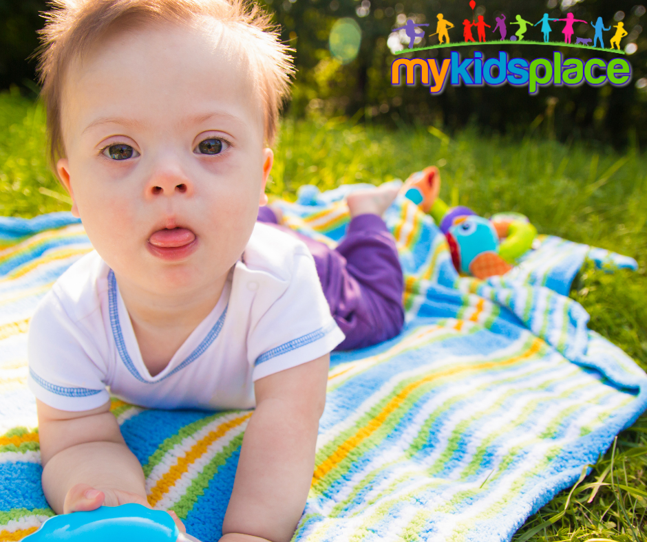 Baby with Down syndrome practices tummy time on a blanket outside