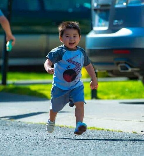 A happy child wearing shorts and a t-shirt is running (an important gross motor skill) with photo taken mid-flight.