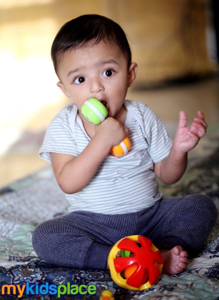 Baby sitting on the floor places a toy in their mouth as a demonstration of sensory play