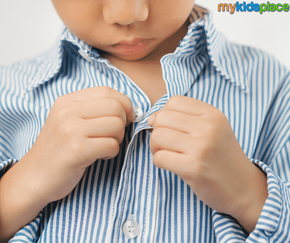 A child in a blue and white striped shirt looks down as they button their shirt using both hands.