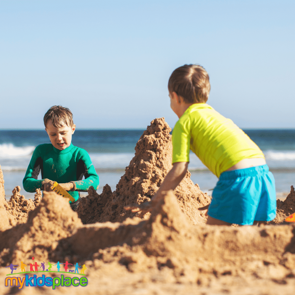 Two children work together to build a sandcastle