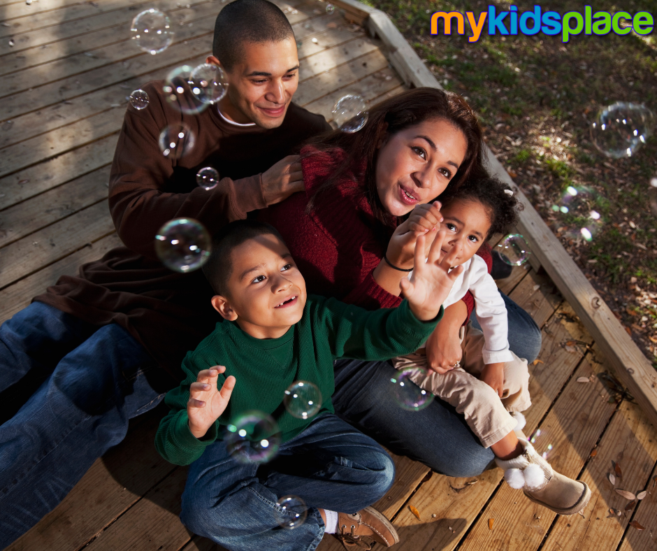 A happy family of 4 plays outside together by blowing bubbles | play child development