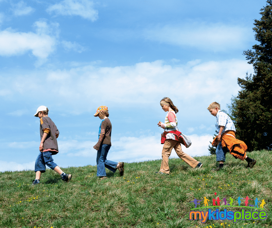 Four children walking across a grass field in different stages of the gait cycle