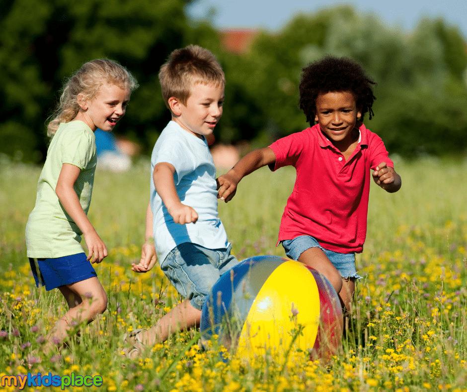 Three children chase a beach ball in a flower field