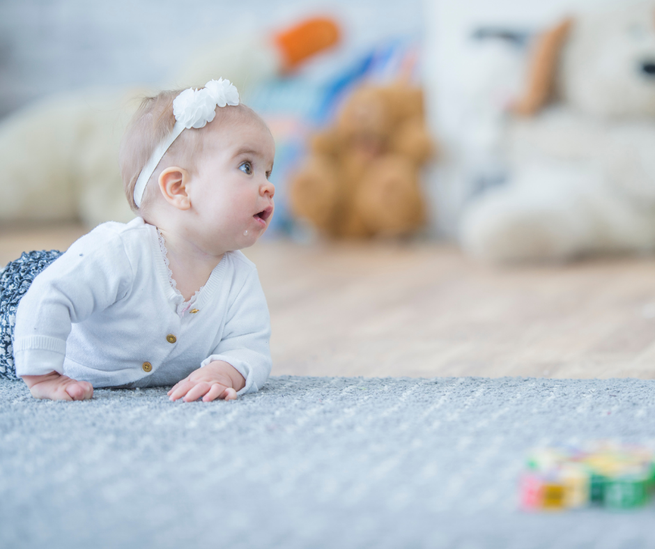 A baby mid-crawl on the carpet looks up to see where they want to go.