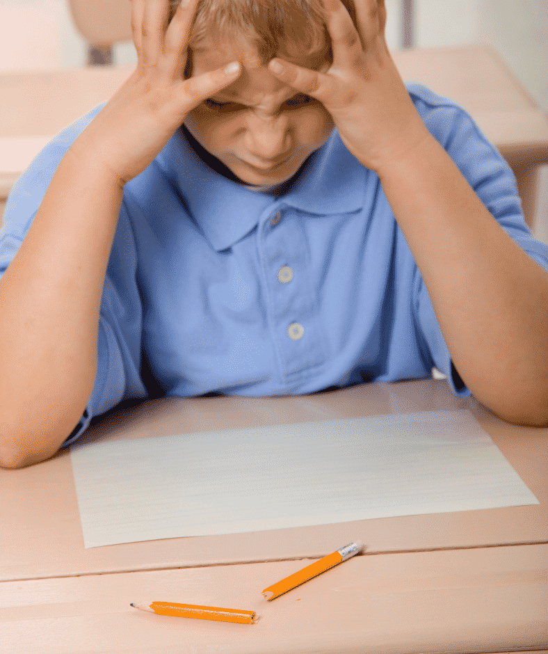 A frustrated child in a blue polo shirt has their hands on their face while they stare at a broken pencil which may have been the result of poor grading of force.