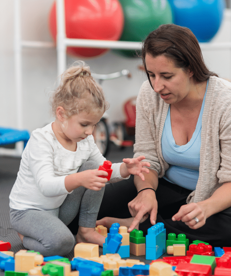 An occupational therapist points to a yellow block where a child can place the red building block they have.