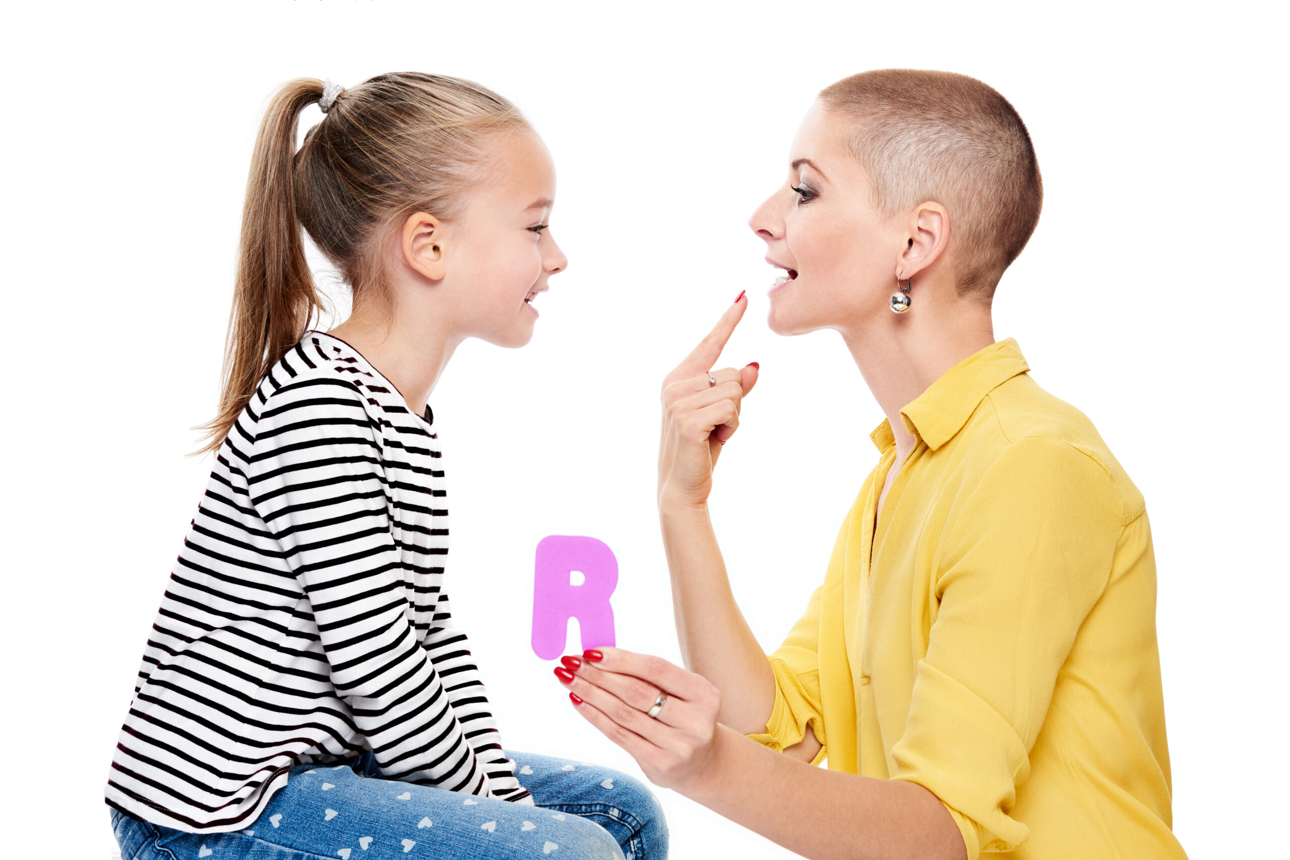 """A speech therapist holds up a letter R while pointing to their mouth and forming the """"r"""" sound. A child watches them closely and tries to replicate the sound."""