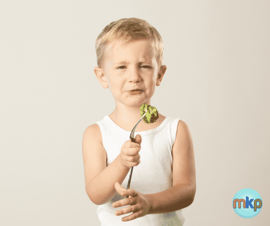 Picky eaters-Grimacing child holds a piece of broccoli on a fork