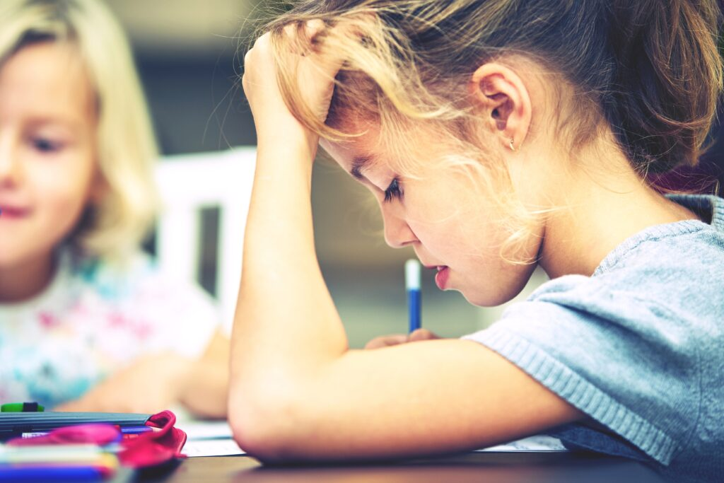 A child at school sits at their desk focusing on their written test.