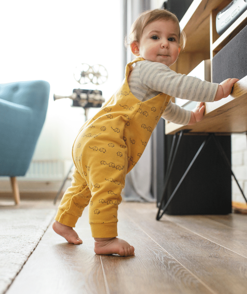 A baby in yellow overalls looks toward the camera as they stand holding onto a TV stand, getting ready to take steps and cruise!