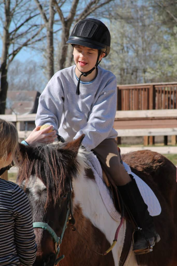 A child in a helmet is helped to ride a brown and white pony as therapeutic intervention.