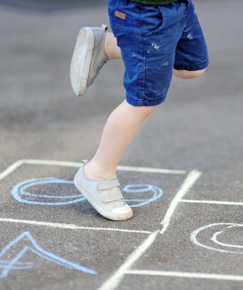 The lower body of a child shown mid-hop on a chalk hopscotch drawing.