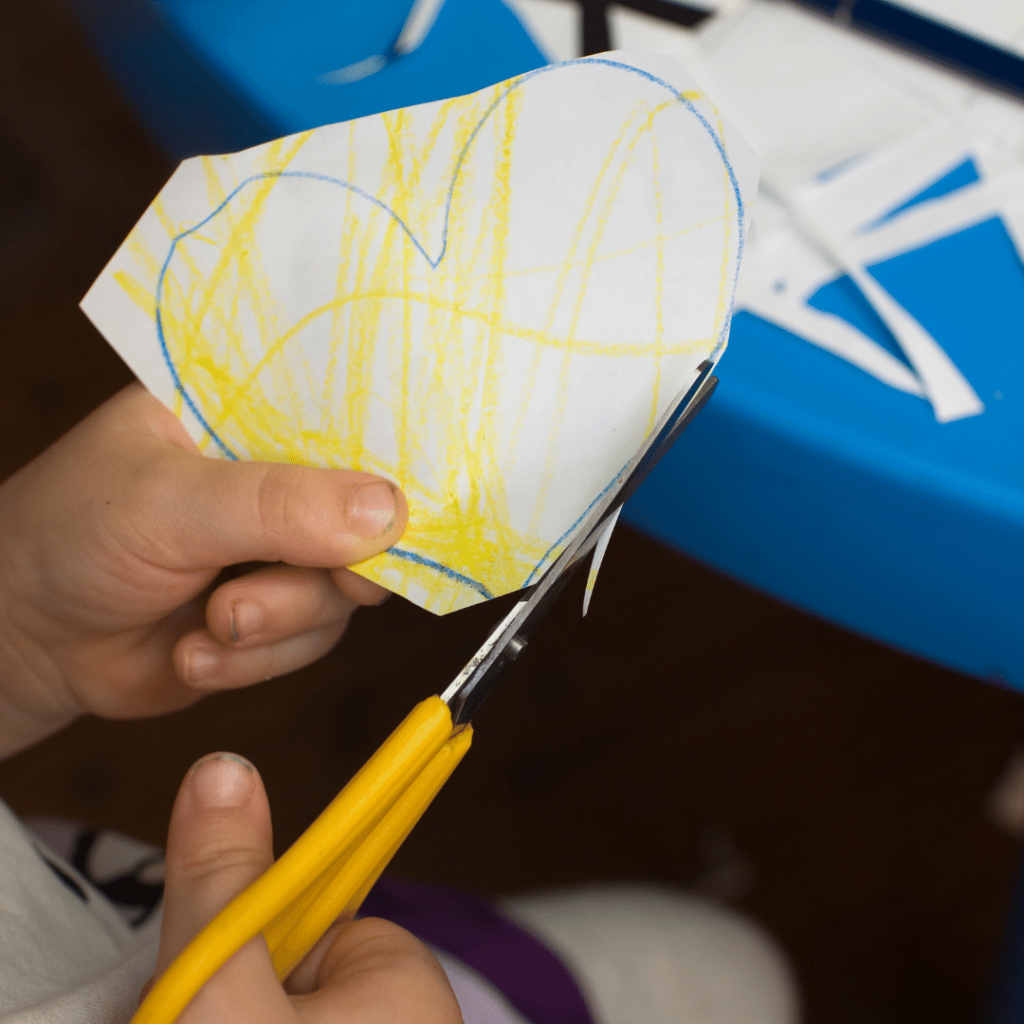 Child's hands holding scissors attempt to cut out a heart outline that has been poorly colored in yellow. The yellow scribbles go outside the blue heart outline. The scissors missed the outline in several places.