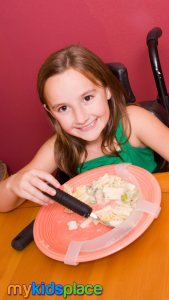 A smiling child in a wheelchair with long brown hair and wearing a green tank top uses an adaptive fork with a wide handle to eat pasta. An adaptive plate guard prevents food from being pushed off the plate and allows the child to pick up the food more easily.
