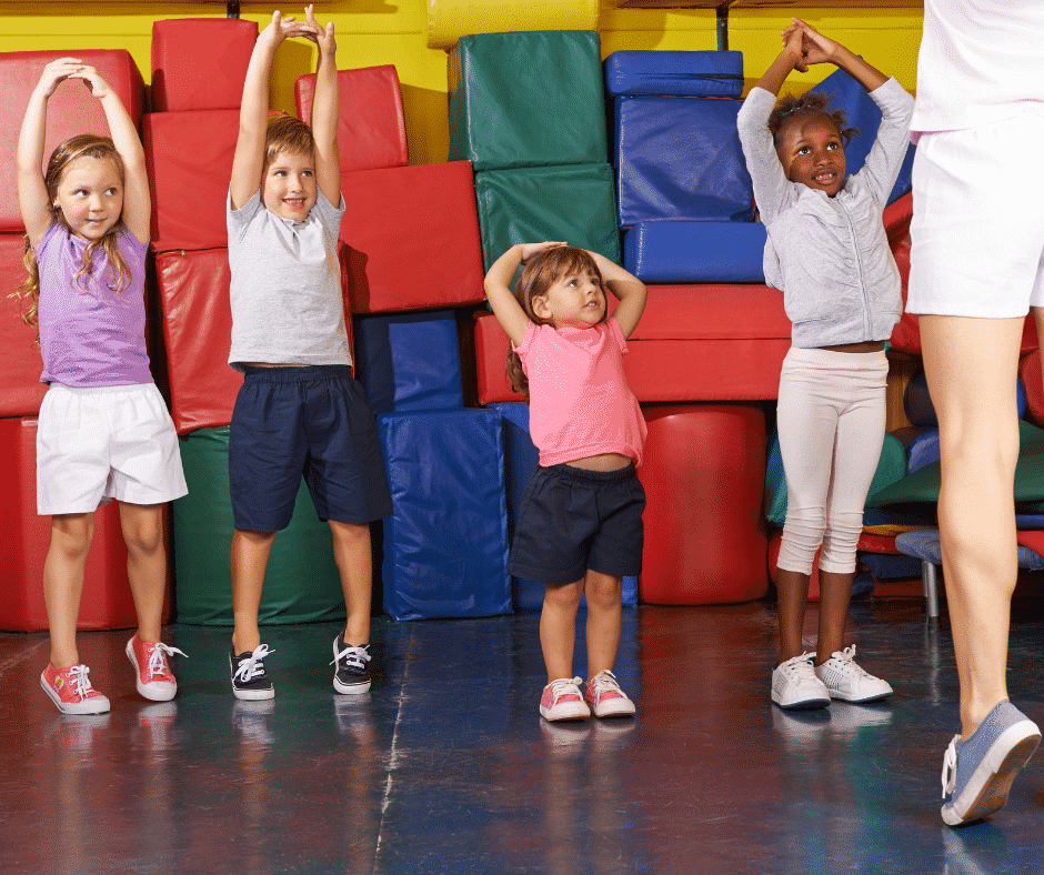 Four smiling children in athletic clothing reach overhead and try to rise onto tip toes as demonstrated by an adult as part of an APE class.