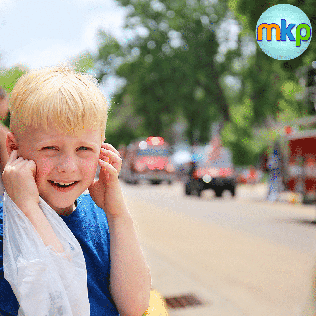 A child standing near a street puts their fingers in their ears and looks at the camera squinting and half smiling. In the street are a fire engine and ambulance with lights on.