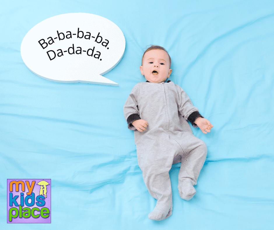 "A baby in a grey onesie lies on their back on a light blue sheet. A speech bubble to their right reads ""Ba-ba-ba-ba. Da-da-da."""